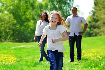 Happy young girl running from her parents