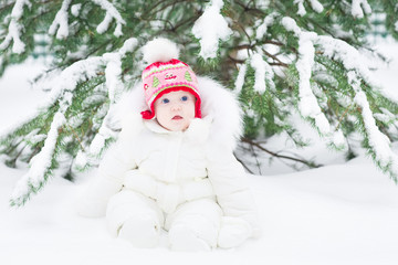 Adorable little baby playing in snow in a winter park