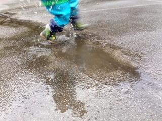 Kind spielt in Pfütze
