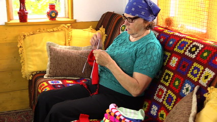 zoom out senior grandmother woman sit on sofa and knit stockings