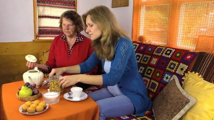 Young pregnant woman drinking herbal calendula tea with grandma