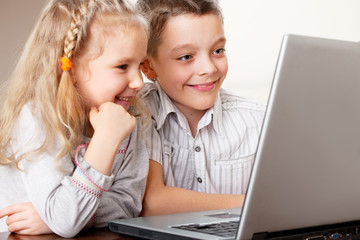 Happy kids playing laptop at home