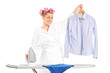 Woman standing behind an ironing board and holding a shirt