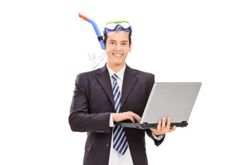 Businessman with diving equipment holding laptop