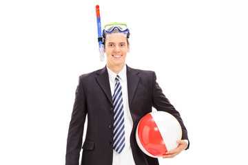 Businessman with snorkeling mask and beach ball posing