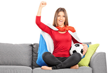 Female sport fan cheering seated on a couch