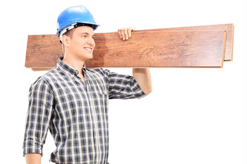 Handsome carpenter carrying a couple of planks