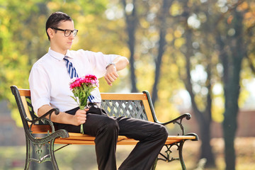 Young man holding flowers and checking the time seated on bench