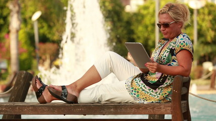 attractive blonde women using digital tablet in park at sunset