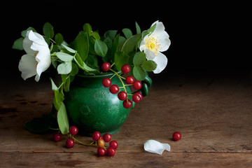 flowers and berries in a vase