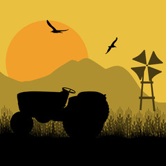 Silhouette of a farm tractor and windmill