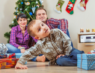 Young family under the christmas tree at home