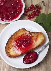Toast of white bread with jam of red currant, a vase with jam an
