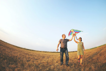 Happy young couple with flying a kite