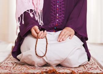 Young muslim girl with rosary praying on white background