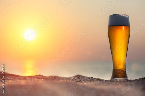 canvas print picture Glass of beer on a sunset