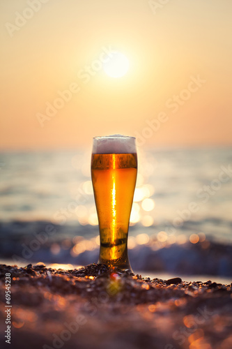 Fotobehang Bier Glass of beer on a sunset