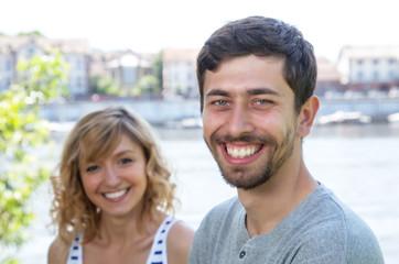 Junges Paar lacht in die Kamera