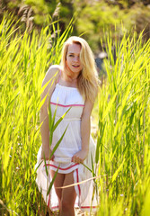 Sensual young woman in white dress posing in green reeds