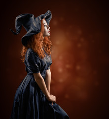 beautiful red-haired girl in the witch costume