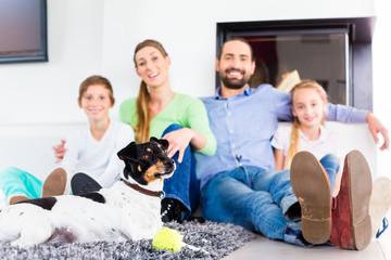 Familie sitzt mit Hund im Wohnzimmer am Kamin