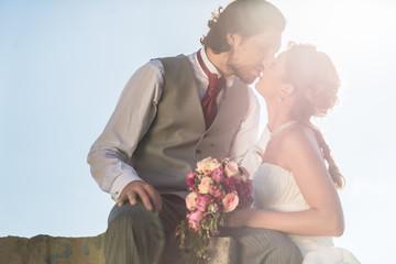 Hochzeitspaar küsst auf einem Feld