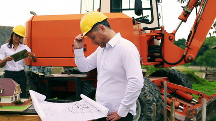 Worried engineer looking on the project and woman using tablet