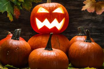 Jack o lantern on pumpkins pile with leaves