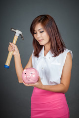 Beautiful Asian girl about to hit money box with hammer