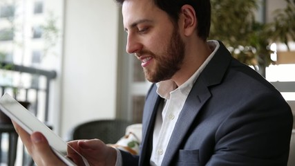 Business Man playing with tablet at home