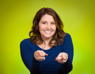 Happy middle aged woman pointing fingers at you camera gesture