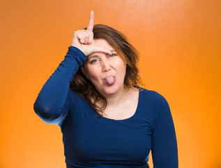 Mad pissed off woman, showing loser sign sticking tongue out