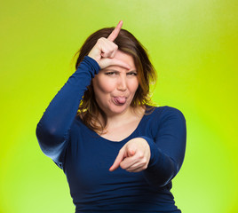 Mad pissed off woman, showing loser sign on green background