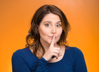 Female showing hand silence sign finger on lips gesture