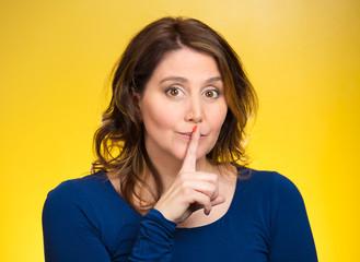 Portrait female showing hand silence shush sign gesture