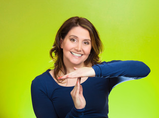 Woman showing time out hands gesture green background