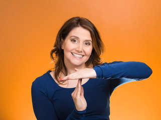 Woman showing time out hands gesture orange background