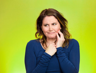 Portrait Woman with sensitive tooth ache on green background