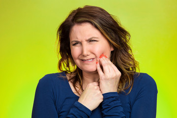 Woman with sensitive tooth ache, on green background