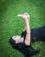 Young woman making selfie while lying in green grass.
