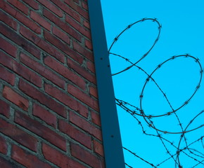 Red brick wall adorned with razor wire