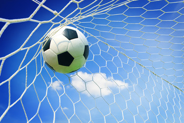 soccer ball in goal with blue sky