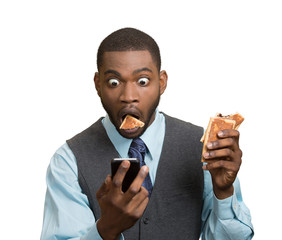 Man reading bad news on smartphone, eating cookie about to choke
