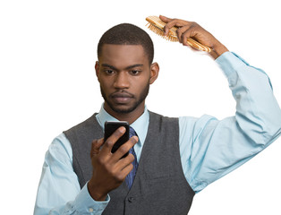 Business man reading news on smartphone, combing hair