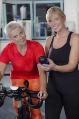 Reife Frauen im Fitness Studio am Spinning Rad besprechen Ernäh