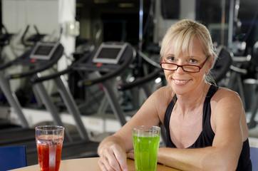 Reife Frau im Fitness Studio an der Bar beim Entspannungsdrink
