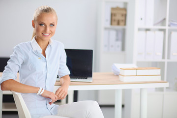 Attractive businesswoman sitting on a desk with laptop in the o