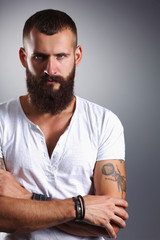 Portrait of handsome bearded man standing with crossed arms, is