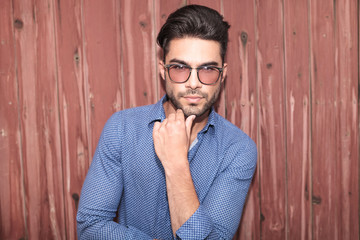 young casual man with glasses thinking