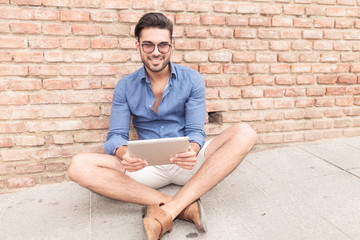 seated casual man with a tablet pad smiling